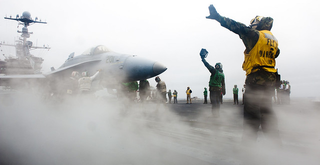 A Sailor directs an F/A-18 Hornet.