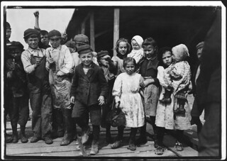All these children except babies shuck oysters and tend babies at the Pass Packing Co., February 1911