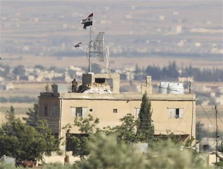 A Syrian solidier stands atop of building as seen from the border with Turkey. Fighting continued on July 2, 2012 in the suburbs surrounding Dasmascus the capital of the Middle Eastern state. by Pan-African News Wire File Photos