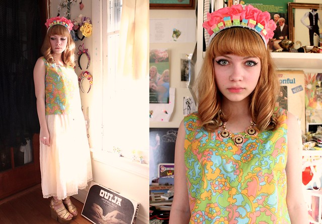 Tavi Gevinson, wearing a mod dress and crown made of fake flowers