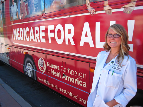 Volunteer Nursing student in front of the Medicare For All bus