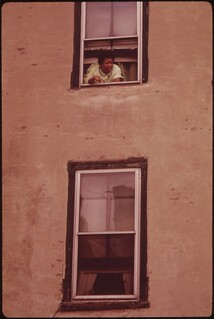 Woman Looks Out Of The Window Of Her Apartment In North Philadelphia, August 1973