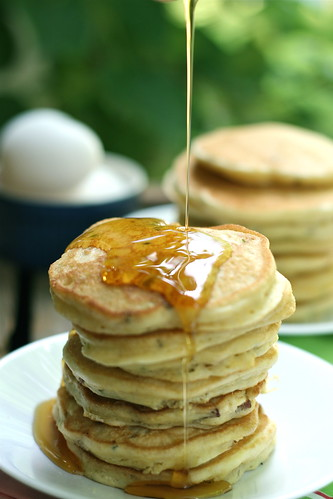 Stack of several corn cakes being covered with a drizzle of syrup.