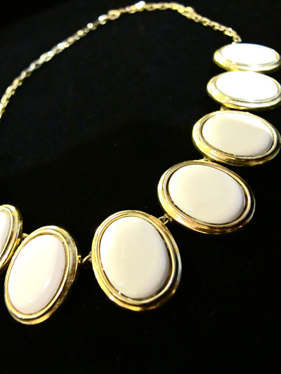 Pretty choker made out of white oval shaped discs and gold accents