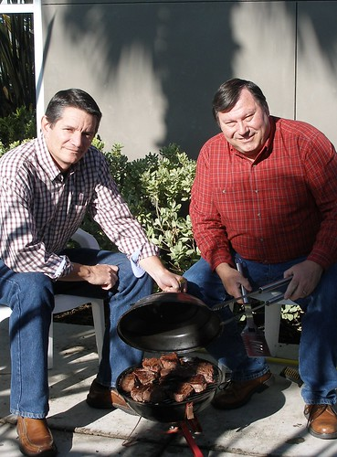 AMS Poultry Program employees Mark Perigen (left) and Gerald Brockman (right) prepare filet mignon on a tailgate-style grill.  They prefer a charcoal grill because of the smoky taste it offers.  Photo courtesy Mark Perigen