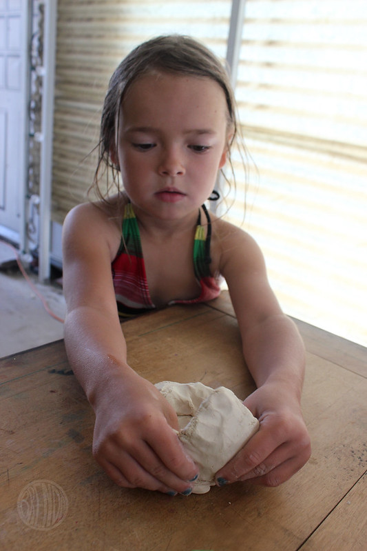 Child forming a monster head with clay