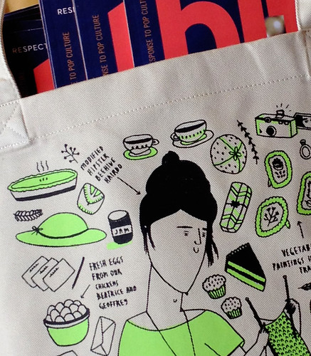 Close-up shot of the tote bag shows text pointing to different items on the bag: the modified hipster beehive hairdo, and fresh eggs from our chickens Beatrice and Geoffrey