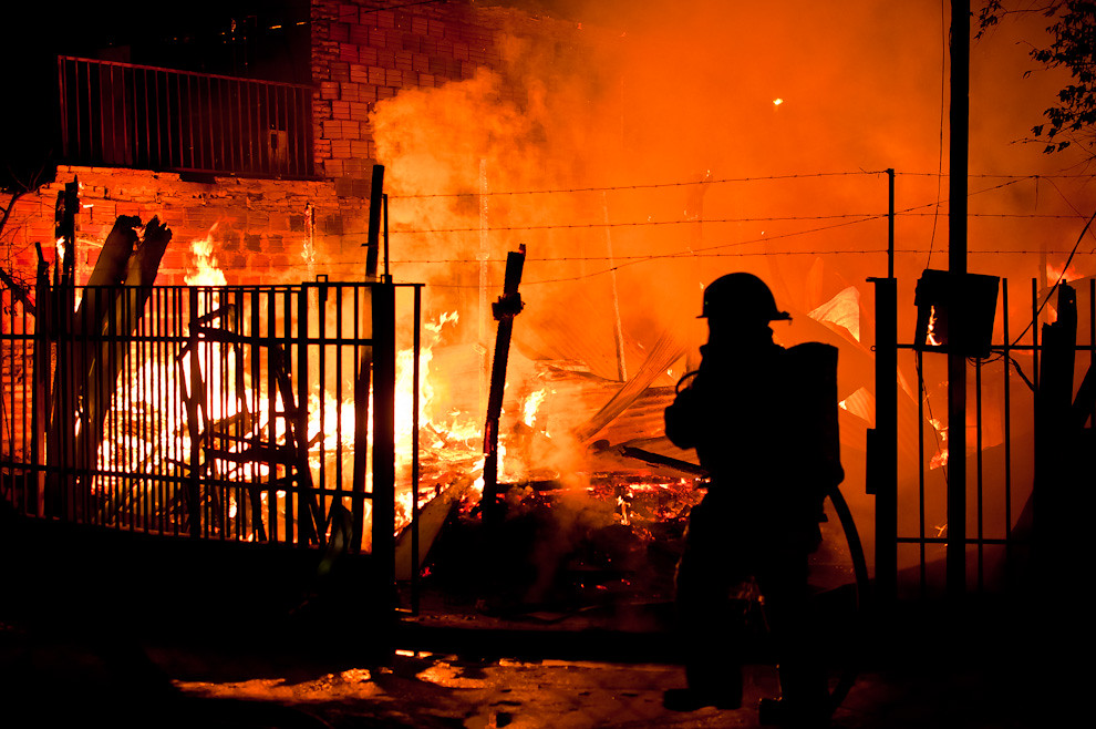 """Una carpintería arde en llamas mientras una mujer bombero apunta su línea de agua hacia el fuego durante un incendio que perjudicó a dos casas en el barrio """"Chacarita"""" en la madrugada del 8 de marzo. Esa noche los bomberos voluntarios trabajaron contínuamente hasta las 7:00 de la mañana aproximadamente debido a un contratiempo con la electricidad que frenó el trabajo. Para el procedimiento de incendios es un requisito cortar la energía eléctrica para poder adentrarse en la casa y hacer los trabajos de extinción y enfriamiento sin que los combatientes corran el riesgo de electrocución. (Elton Núñez)"""