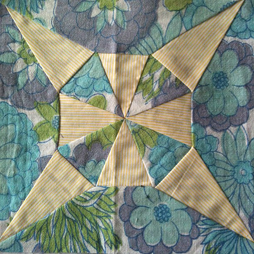 Dear Jane block made from blue vintage floral fabric and yellow striped fabric