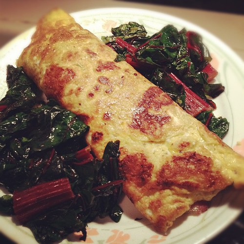 Egg tortilla stuffed with veggies and surrounded by Swiss chard. #paleo #primal