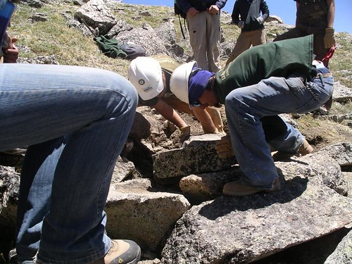 Members of the Rocky Mountain Youth Corps lift heavy boulders as part of a project to turn user-created trails on Mount Yale in Colorado into properly maintained trails that do not hurt the environment. (U.S. Forest Service Photo)