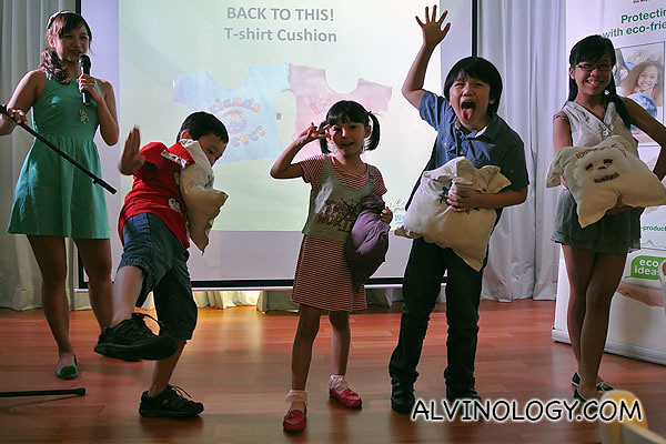 A group of kids showing off their tee-shirt pillows on stage