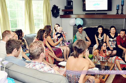 some of the guests gathered around the TV for the gender reveal wives tales game - adorkableduo.com