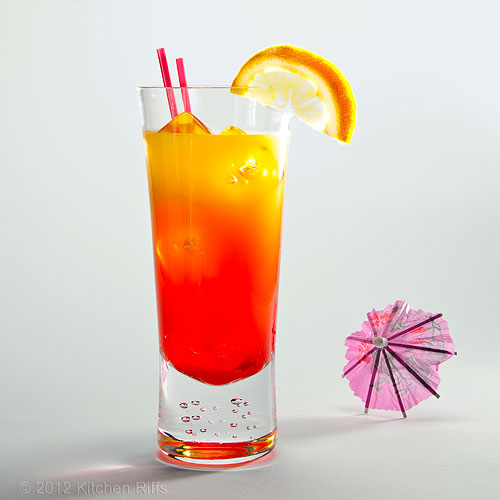 Tequila Sunrise Cocktail in Tall Glass with Orange Slice, White Background