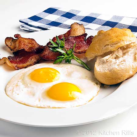 Fried Eggs on Plate with Bacon and Biscuits