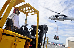 "NORTH SULAWESI, Indonesia  (May 31 2012) Logistics Specialist 3rd Class Harlan Esmailka waits in a fork lift as an MH-60S Sea Hawk helicopter, assigned to the ""Blackjacks"" of Helicopter Sea Combat Squadron (HSC) 21, delivers three pallets of medical supplies to Military Sealift Command hospital ship USNS Mercy (T-AH 19). (Photo released by Kristopher Radder)"