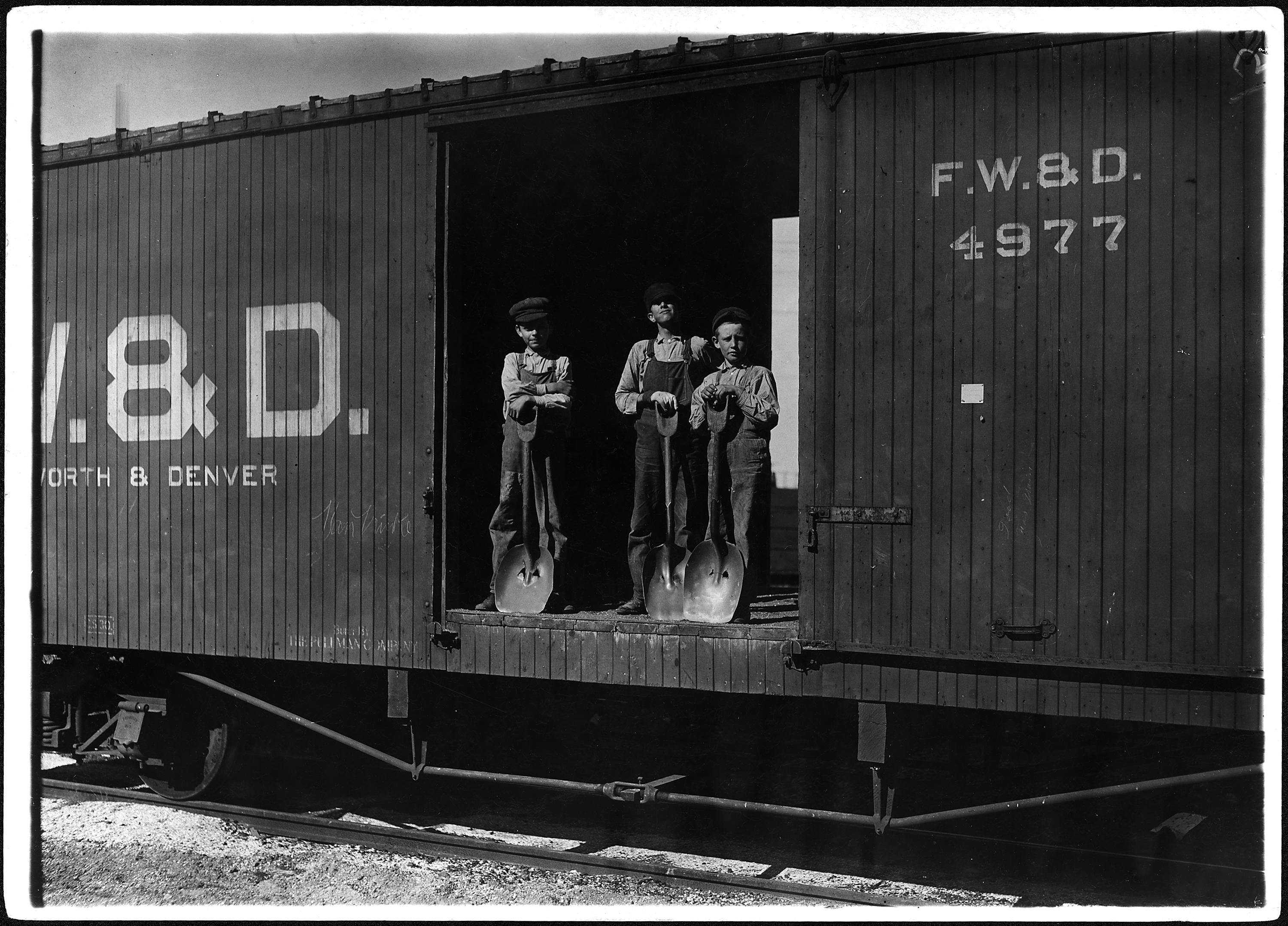 Three young boys with shovels standing in doorway of a Fort Worth & Denver train car, 1912