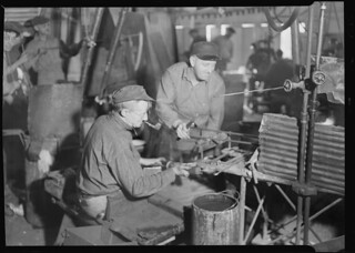 Glass bottles. T. C. Wheaton Co. A gaffer finishing a wide mouthed bottle, March 1937