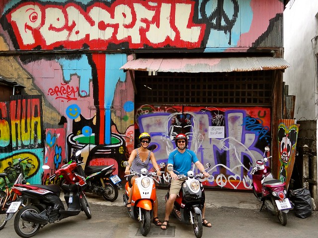 Mom and dad on motorbikes with street art