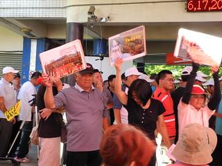 反對民眾高舉海報佔據發言台抗議。