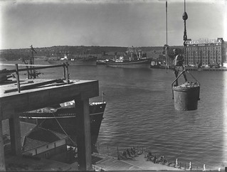 View of shipping wharves in Sydney Harbour with a construction worker standing in the bucket of a crane in the foreground