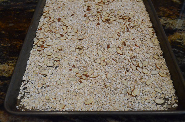 Oats and almonds spread out into a thin layer on a rimmed baking pan.