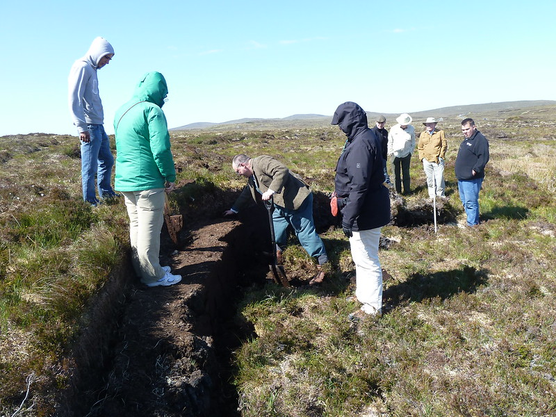 Tour group cutting peat on Isle of Lewis, Scotland