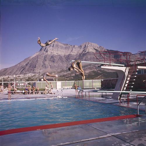 Three children diving into outdoor pool / Trois enfants plongeant dans une piscine extérieure