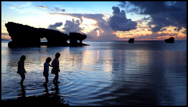 KIDS AND THEIR MOM IN SILHOUETTE AS THEY WALK ACROSS THE SUNSET TIDAL FLATS in OKINAWA