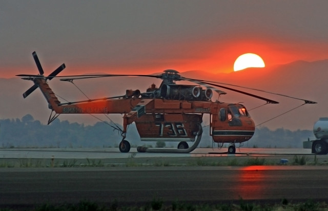 The sun rises behind a skycrane at Los Alamos Airport on the smoky morning of July 4th.  Photo by Ethan Frogget.