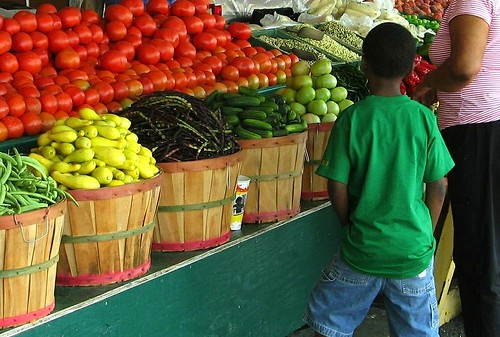 A young boy looking over the fresh fruits and veggies with his mother at a farmers market in Mississippi.