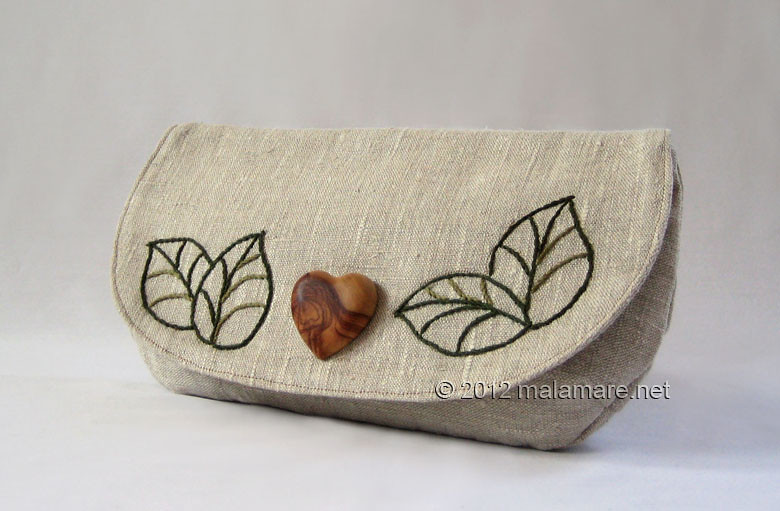 natural linen fabric clutch bag with olive wood heart and hand embroidered leaves motif
