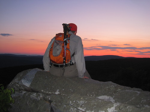 man sitting on rock looking at sunset wearing Granite Gear backpack