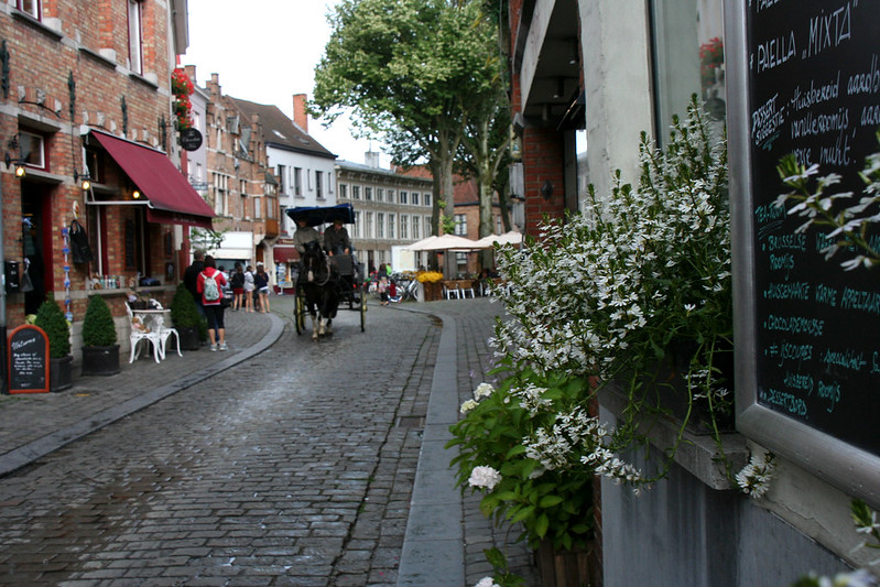 cobblestone street in Brugge with horse-drawn carriage