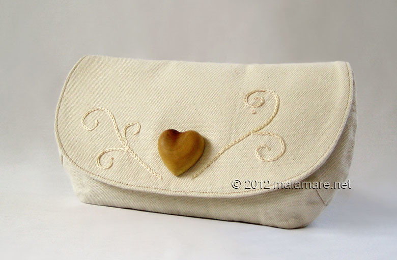 ivory cotton fabric clutch bag with olive wood heart and hand embroidered swirls motif