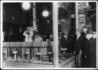 7 year old Tommie Nooman demonstrating the advantages of the Ideal Necktie Form in store window, April 1911
