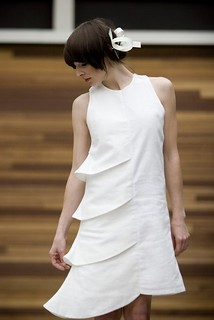 a woman in an asymmetrical white dress