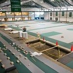 12-07-01 -- JULY 2012: Workers are busy installing a new laid rubber surface in the Shirk Activity Center, where the track and all courts are being resurfaced. The material is nearly identical to that being used in the London Olympics this month.