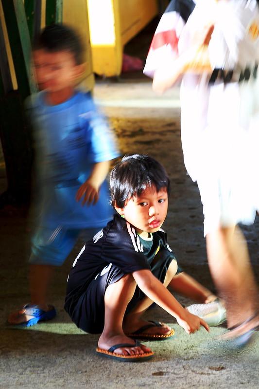果菜市集中孩童在攤架構成的城堡間嬉鬧