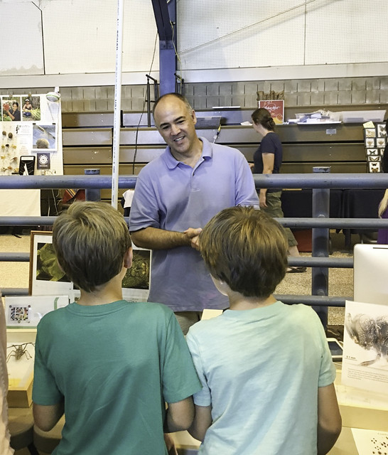 Andy Deans stands at the Frost Museum table and speaks with two boys about wasps