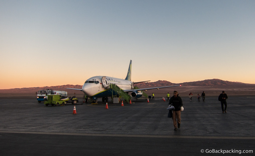 Passengers walk off the Sky Airlines plane on the tarmac at El Loa Airport at sunset