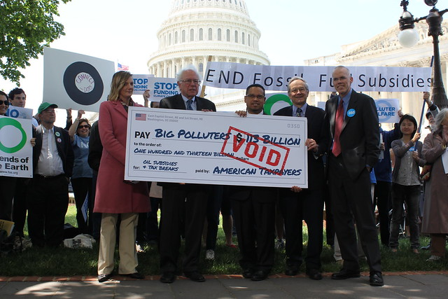 Rally speakers hold up the fossil fuel industry's voided check