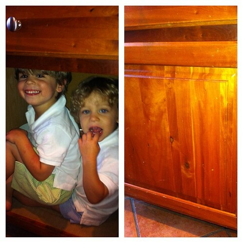 Why yes, 2 kids can fit in a closed kitchen cabinet