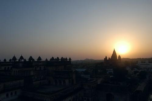Die Sonne geht hinter dem Shiva Tempel von Orchha unter, im Vordergrund sind die Pavillions des Palastdachs