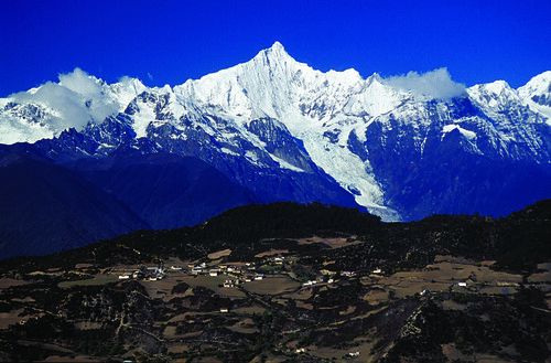 The sacred Khawa Karpo Peak looms above Feilaisi village in northwest Yunnan. Photograph by Robert Moseley.