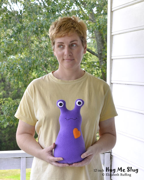 Purple fleece Hug Me Slug, with an orange heart, original art toy by Elizabeth Ruffing, also pictured