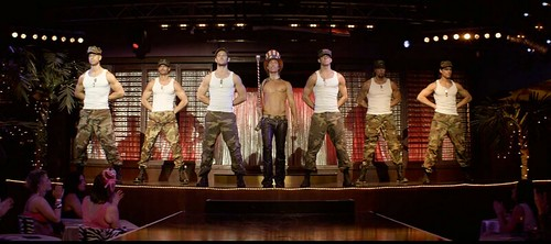 the cast of magic mike onstage performing a military number