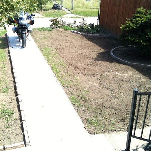 Stone edging is done. Soil is raked. Ready to plant grass.