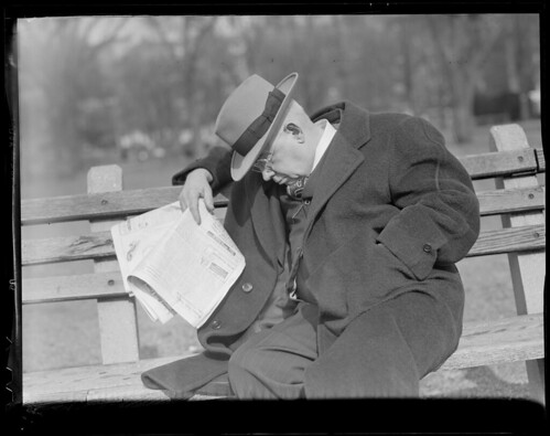 Man on bench reading paper
