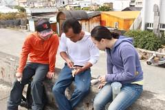 和部落木藝老師在堤防上看著海,學習雕刻木湯匙